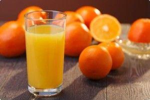 Апельсиновий сік у склянці і апельсини на столі