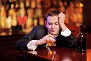 Чоловік сидить в барі і п`є алкоголь